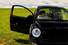 Relaxing In A Field. A man and a woman sit back in their car and listen to music in a quiet field Stock Image