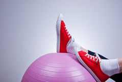 Relaxing with fitness ball. Female legs wearing red trainers kept on purple fitness ball, relaxing after workout Royalty Free Stock Image
