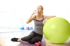 Relaxing after fitness workout. Portrait of middle age sporty woman sitting next to her fitness ball while drinking a bottle of water Royalty Free Stock Images