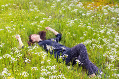 Woman relaxing flower field. Pretty woman relaxing on the flower field. Stress free Stock Photography