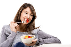 Relaxing with a fruit salad. Beautiful woman relaxing on the sofa and eating a fruit salad Stock Image