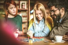 Relaxing game. Three friends at cafe. Three young people playing leisure game. Three friends at  cafe Royalty Free Stock Photo