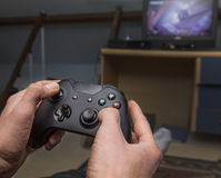Relaxing on gaming machine in loft. Teen in den playing with gaming controller on tv Royalty Free Stock Photos