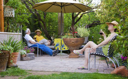 Relaxing in the garden. People drinking red wine in a garden patio Stock Images