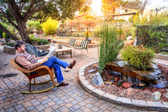 Relaxing in a garden. Man is reading a newspaper on a patio in a cozy garden Royalty Free Stock Image