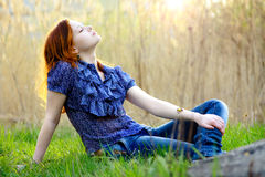 Relaxing girl. A woman on the grass field and a sunset royalty free stock photography