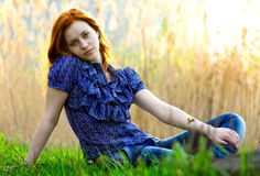 Relaxing girl. A woman on the grass field and a sunset stock images