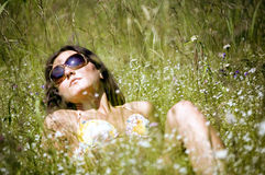 Relaxing girl on a meadow. The girl has a rest under the sun lying on a meadow Royalty Free Stock Image