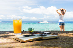 Relaxing girl, opened empty notepad is on the table with sunglasses, phone and headphones at the tropical sea background Stock Photo