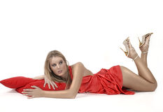 Relaxing girl in red dress. Picture of girl relaxing on red pillows Royalty Free Stock Images