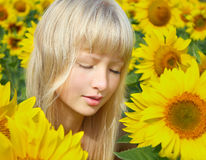 Relaxing girl among sunflower field Royalty Free Stock Photos
