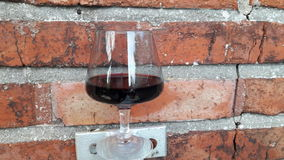 Relaxing with a glass of red wine. A glass of red wine with vintage  brick texture wall Royalty Free Stock Image
