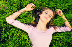 Relaxing in grass. Pretty girl in pink blouse relaxing while lying in grass Royalty Free Stock Photo
