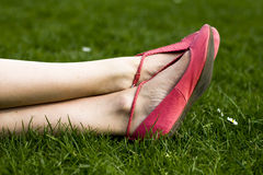 Relaxing on the grass. Close up of a woman's feet and shoes as she lies in the grass on a summer's day Royalty Free Stock Image