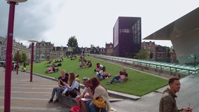 Relaxing on the greens of Museum Square - large meadows to lie on - AMSTERDAM - THE NETHERLANDS - JULY 19, 2017. Relaxing on the greens of Museum Square - large stock video