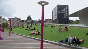 Relaxing on the greens of Museum Square - large meadows to lie on - AMSTERDAM - THE NETHERLANDS - JULY 19, 2017. Relaxing on the greens of Museum Square - large stock video footage