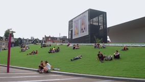 Relaxing on the greens of Museum Square - large meadows to lie on - AMSTERDAM - THE NETHERLANDS - JULY 19, 2017. Relaxing on the greens of Museum Square - large stock footage