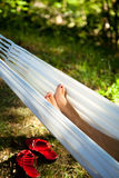 Relaxing in a Hammock. Feet of a woman in a hammock at sunset Royalty Free Stock Photography