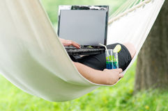 Relaxing on hammock. Man working on laptop during holiday Royalty Free Stock Image
