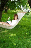 Relaxing on hammock. Young woman relaxing on hammoch with drink Stock Photo