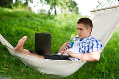 Relaxing on hammock. Man working on laptop during holiday Stock Photography