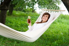 Relaxing on hammock. Young woman with drink on hammock Stock Image