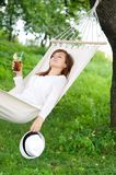 Relaxing on hammock. Young woman with drink on hammock Stock Photos