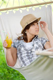 Relaxing on hammock. Young woman with drink on hammock Royalty Free Stock Photo