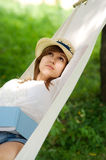 Relaxing on hammock. Young woman relaxing on hammock with book Stock Photo