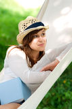 Relaxing on hammock. Young woman relaxing on hammock with book Stock Images