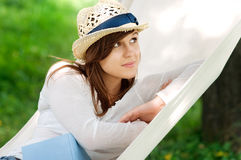 Relaxing on hammock. Young woman relaxing on hammock with book Royalty Free Stock Images
