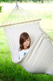 Relaxing on hammock. Young woman reading a book in hammock Royalty Free Stock Photo