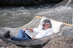 Relaxing in hammock. A retired man reading a book peacefully on a hammock hung near a mountain river Royalty Free Stock Photography
