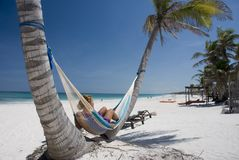 Relaxing on the hammock. Young woman relaxing on the hammock on a tropical beach Stock Photo