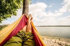 Relaxing in the hammock at the beach under trees, summer day Royalty Free Stock Photo