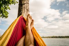 Relaxing in the hammock at the beach under trees, summer day Stock Photo