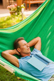Relaxing in hammock. Happy mature man sleeping while lying in hammock with book laying on his torso Stock Image