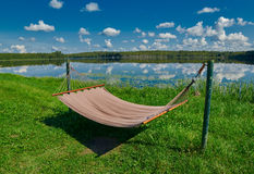 Relaxing Hammock on a lake shore under summer sunshine Royalty Free Stock Photo