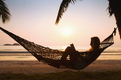 Relaxing in hammock. Silhouette of woman relaxing in hammock on the beach Royalty Free Stock Images
