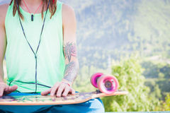Relaxing and handsome hipster man listening to music with skateboard Royalty Free Stock Photography