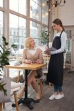 Inspired woman making an order. Relaxing. Happy aged women sitting in a cafe and making an order Royalty Free Stock Photos