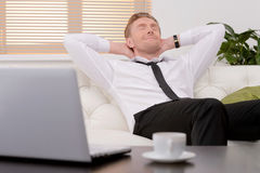Relaxing after hard working day. Cheerful young businessman rela Royalty Free Stock Image