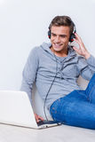 Relaxing with her favorite music. Happy young man in headphones listening to the music and looking at laptop while sitting on the floor with laptop near him Royalty Free Stock Photo