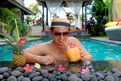 Relaxing on holiday. Handsome man relaxing in swimming pool and drinking coconut cocktail at a luxury villa on Bali island stock photos