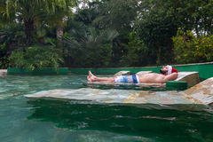 Relaxing holiday vacations. Young man laying down in natural hot springs in tropical Costa Rica with a red holiday hat royalty free stock image