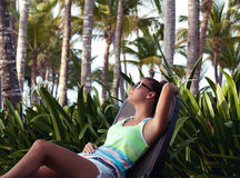Relaxing while on holiday. Young woman reclining on a deck chair with her hand behind her head. Girl at travel spa resort, Dominican Republic stock photography
