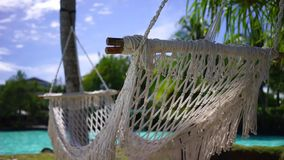 Relaxing Holidays. A close up of an empty hammock swaying with the cool and relaxing wind on a tropical holiday resort stock footage