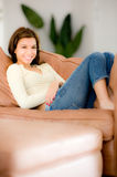 Relaxing At Home. A young woman sitting in a comfortable chair at home royalty free stock photos