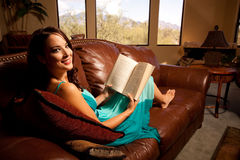 Relaxing at home with a book. This attractive young lady relaxes whilst reading a book on this huge leather couch Royalty Free Stock Photo
