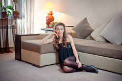 Relaxing at home. Portrait of a young woman smiling. On white couch royalty free stock images